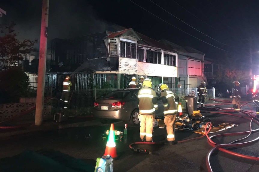 Fire crews surround a house blackened by fire at night