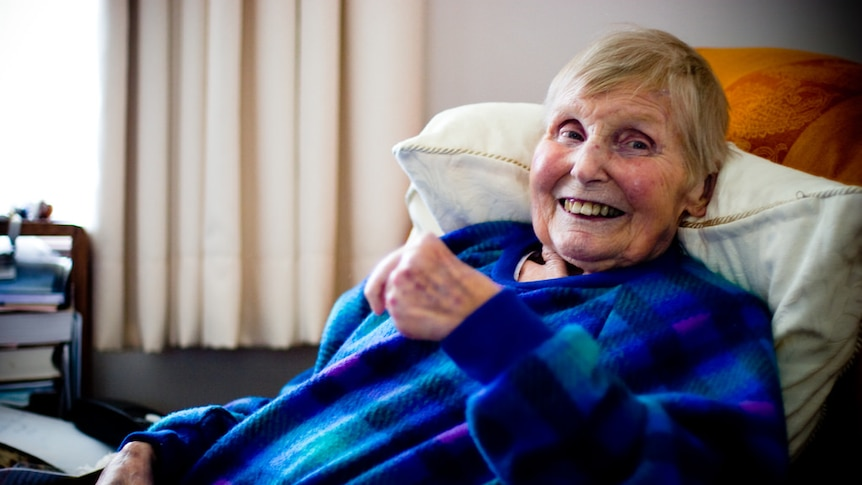 A older woman sitting with a cup of tea in her dressing gown and smiling.