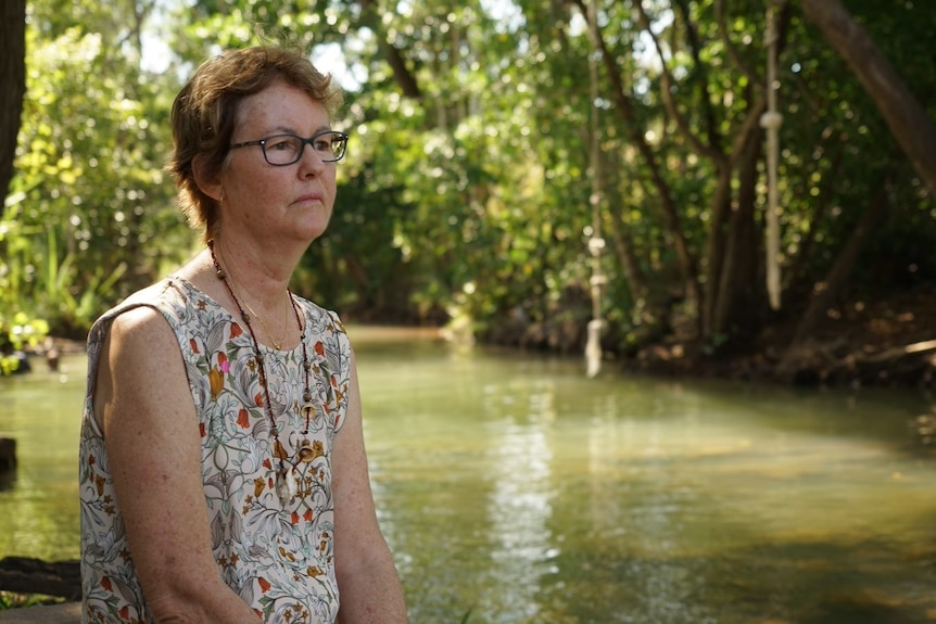 A woman wearing a mournful look sits facing a creek in Darwin.