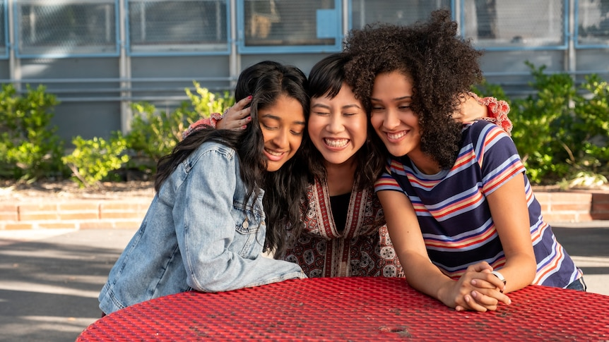 Three teenage girls sit and hug at a red table outside