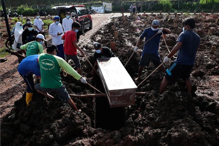 Pekerja menurunkan peti mati ke kuburan berlumpur