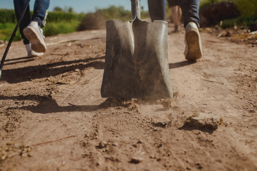 A shovel drags on the dirt road.