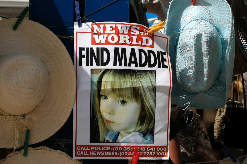 A poster of missing girl Madeleine McCann hangs between sun hats at a stall.
