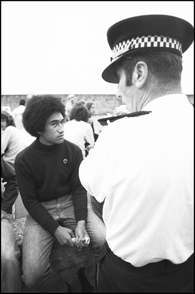 A young Pacific man looks into the eyes of a police officer standing over him.