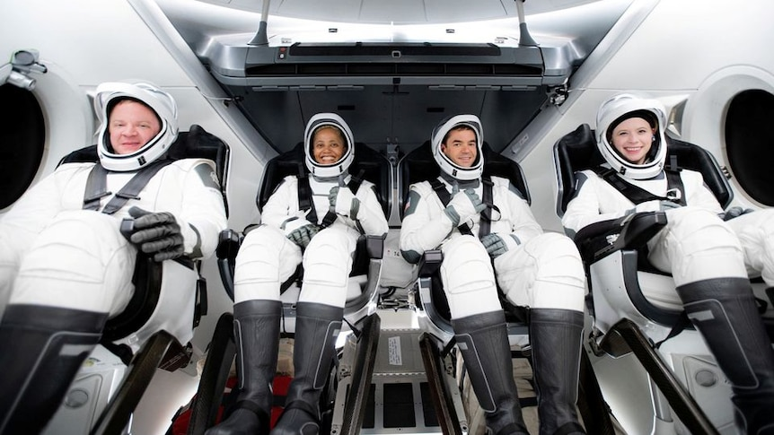 Civilian astronauts wearing white gear and helmets sitting in a space ship ready for take off.