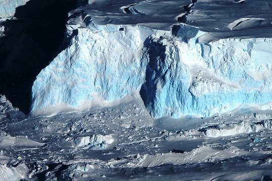 An aerial view of a bluish-white giant glacier with craggy sides and a snowswept top