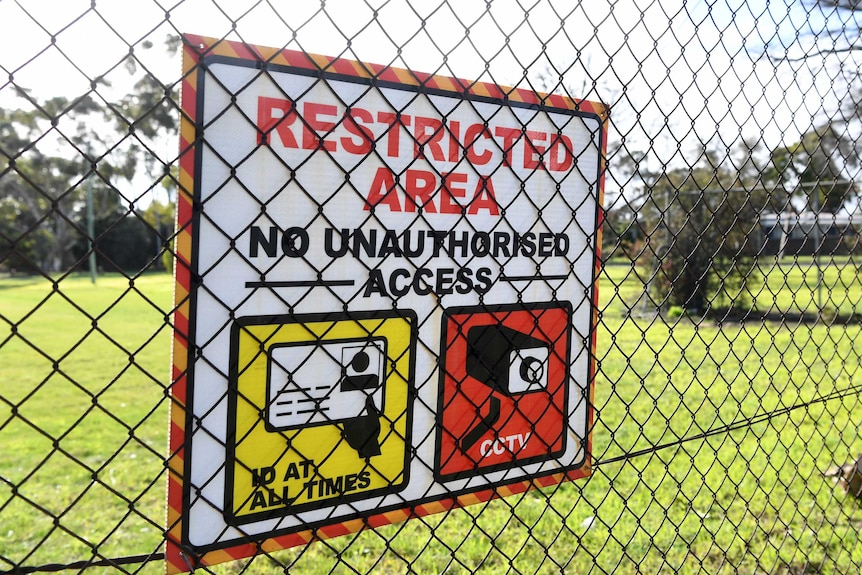 "A sign that says ""restricted area"" is fixed to a chain link fence in front of green grass."