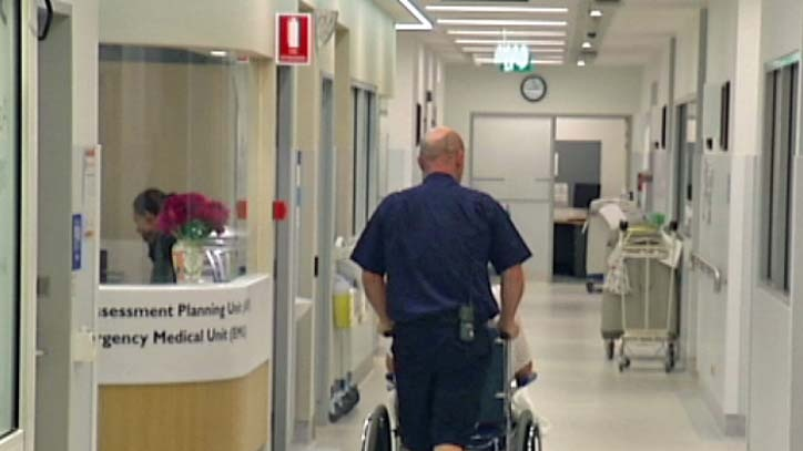 A man pushes a patient in a wheelchair.
