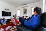 A profile of Anthony, not his real name, sitting on the couch at home.