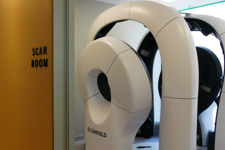 A tall machine made of loops of cameras standing in the background, inside a room marked 'Scan room'.