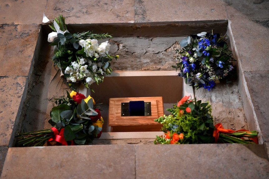 Bunches of flowers placed around ashes laid in a hole in the ground.