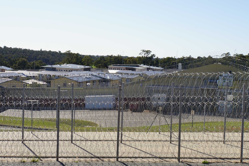 Wide shot of buildings in Acacia Prison, with barbed wire fences in the foreground and bushland behind the prison.