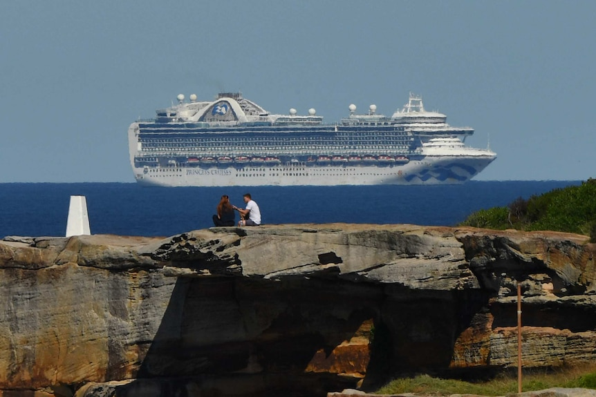 A couple sit on a rock with the ship on the horizon