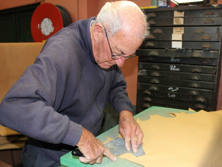 Long-time employee 75-year old Max Redman cutting leather by hand at the Baxter Boots factory in Goulburn, NSW.