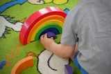 A child plays with a wooden block toy shaped like a rainbow