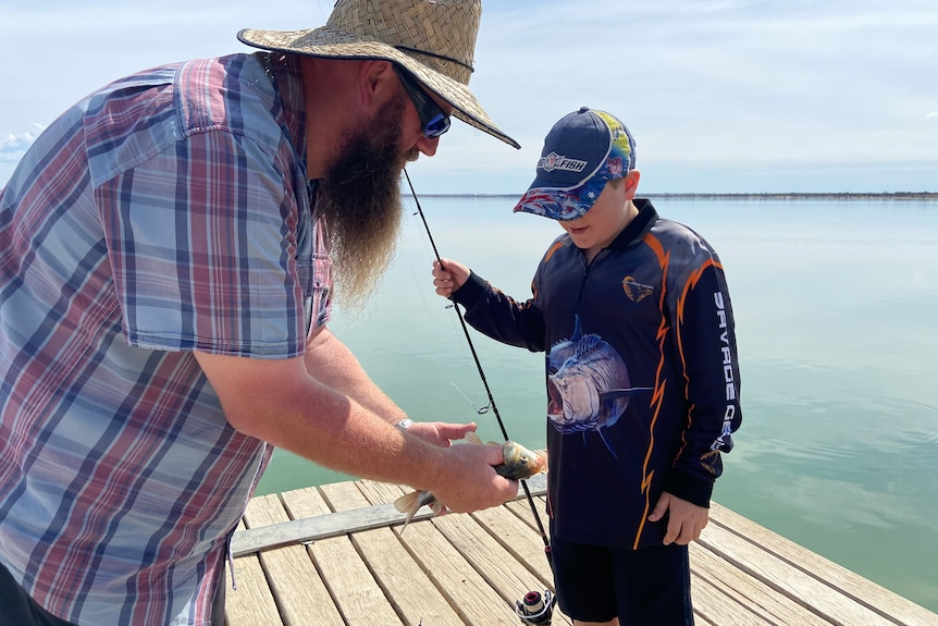 A man with a checked shirt, beard and straw hat holds a fish as a boy with a long sleeve top and cap watches on a jetty.