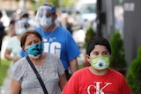 People wear different coloured masks as they wait in a line outside.
