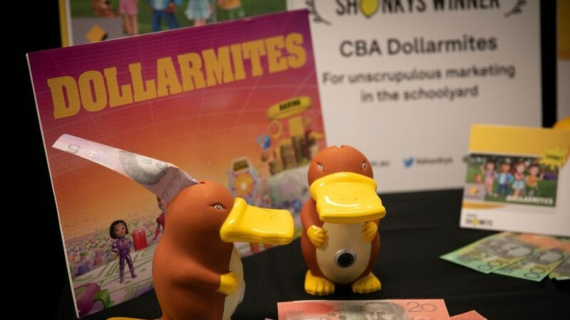 Two platypus moneyboxes with five, ten and twenty dollar notes around them and an award certificate in background.