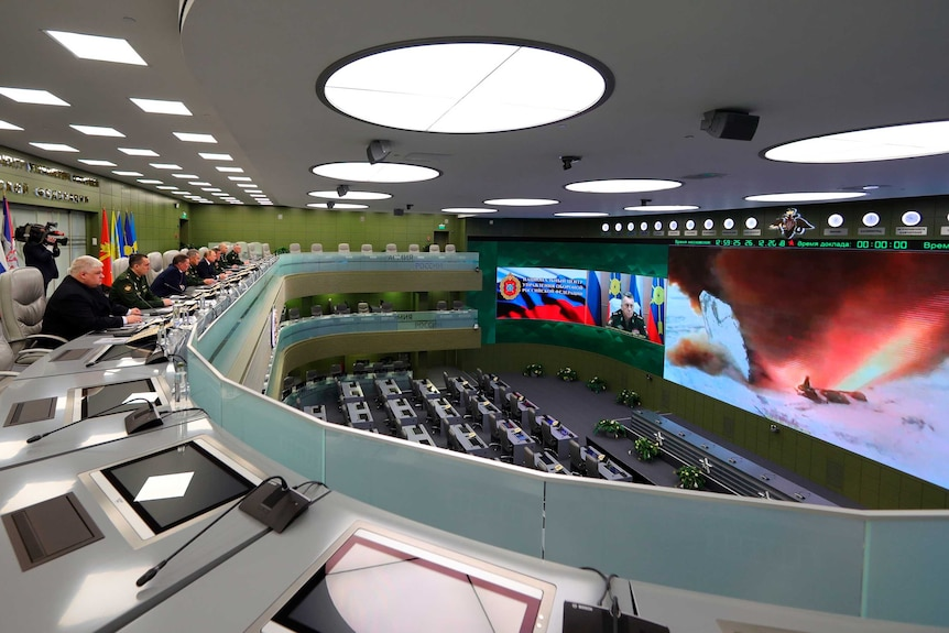 Russian weapons test explosion is seen on screen as government officials look on.
