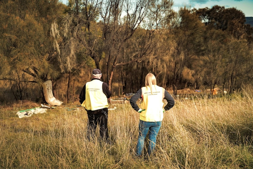 Two people survey rubbish in a field
