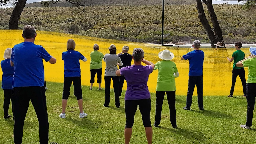 A group of men and women stand facing away from the camera during a tai chi class for a story about tai chi exercise benefits.