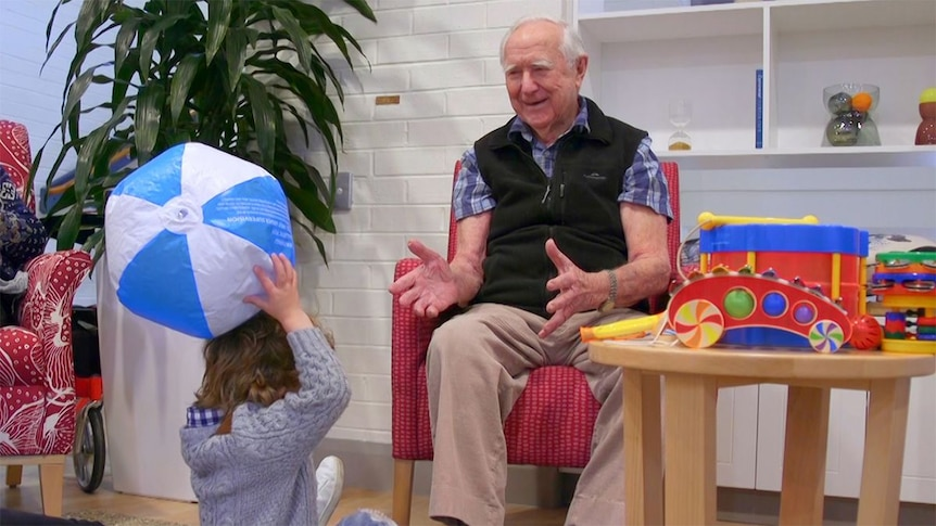An elderly man sits on a chair playing with a young toddler.