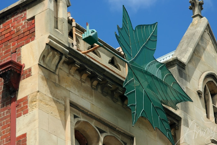 Image of sculpture of hand with middle finger on top of a ledge on an old building