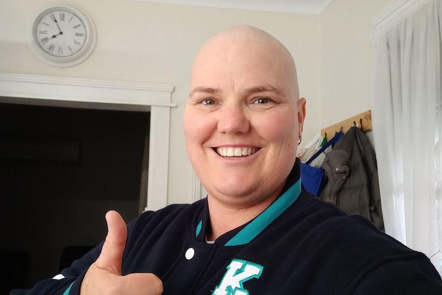 A woman who has undergone cancer treatment gives a thumbs up and smiles.