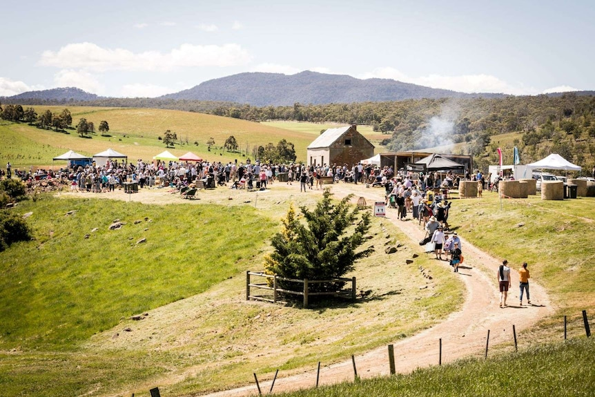 a crowd of people in a field with historic farm shed in background