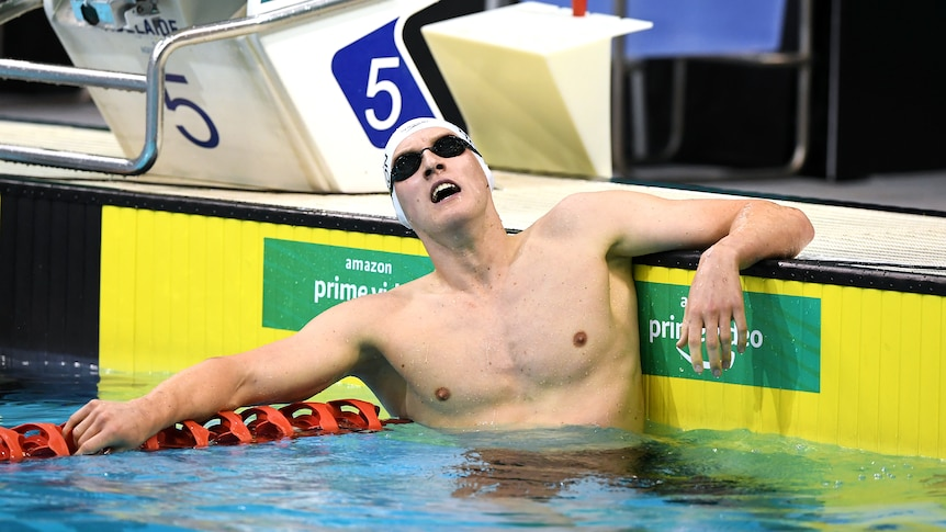 Australian swimmer Mack Horton, in cap and goggles, looks tired in the pool after the 400m freestyle final at the Olympic trials