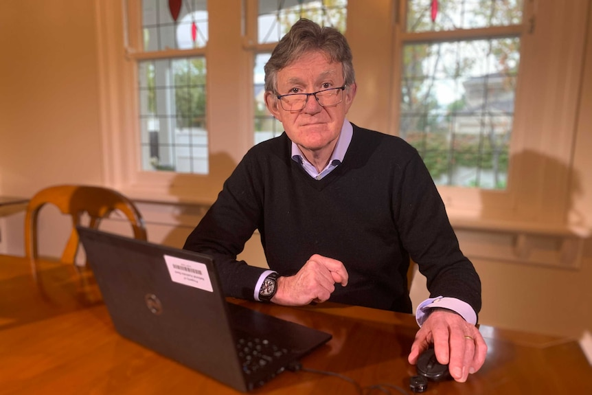 Alan Oster, in glasses, collared shirt and jumper, sits at a wooden dining table with his laptop open in front of him