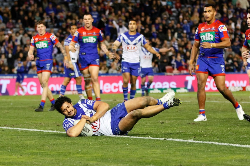 Corey Harawira-Naera lies on his side while grounding the ball. A group of players watch on behind him.