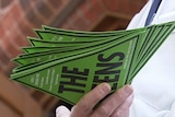 A hand holds a bunch of stickers for the Greens