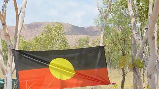 The black red and yellow flag hangs between two trees