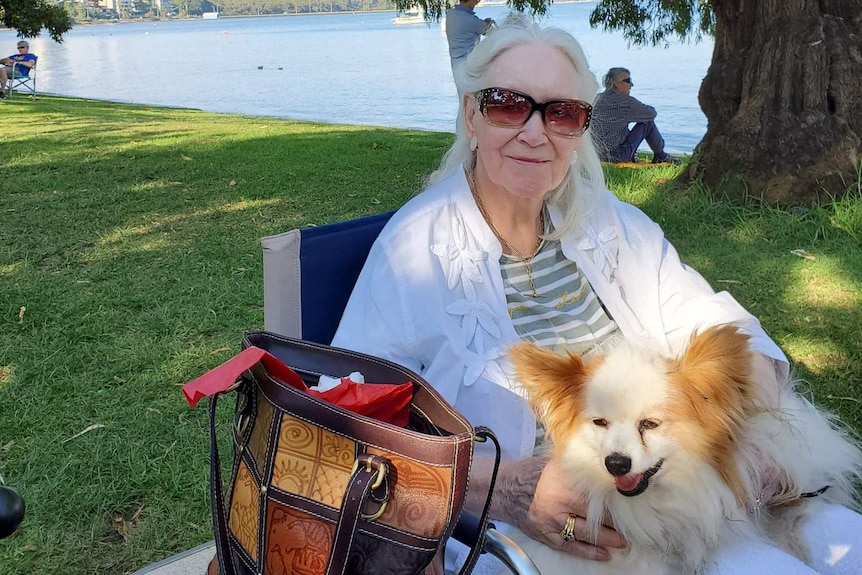 An older lady in sunglasses at the river, holding a dog.