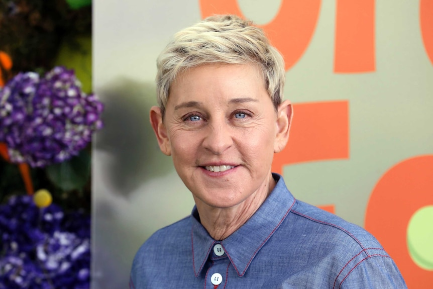 A headshot of talk show host Ellen DeGeneres, she is smiling and wearing a blue buttoned up short
