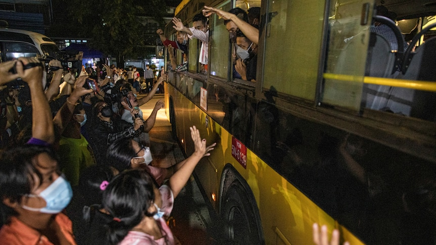 People wave to passengers on a bus.