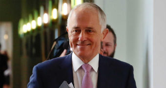 Prime Minister Malcolm Turnbull smiles as he walks through the halls of Parliament House holding his ipad