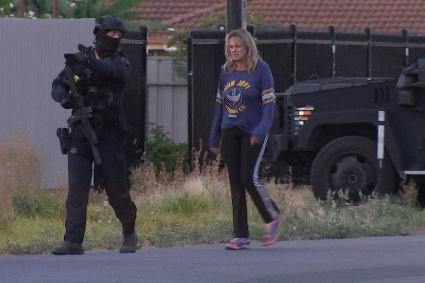 A woman walks next to a Star Force officer