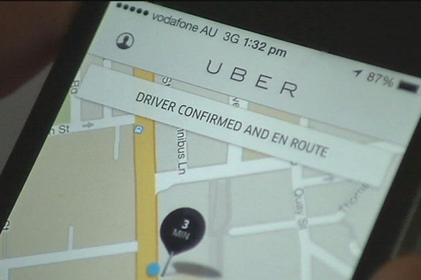 """A photo of a phone screen with the """"Uber"""" app open, showing a GPS map"""