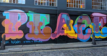 Brightly coloured street art depiction of the word 'place' against a large, black wall.