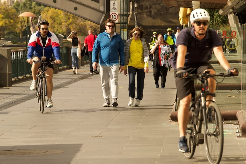 Pedestrians and cyclists move along the path outside Southgate, along the Yarra River just south of Melbourne's CBD.
