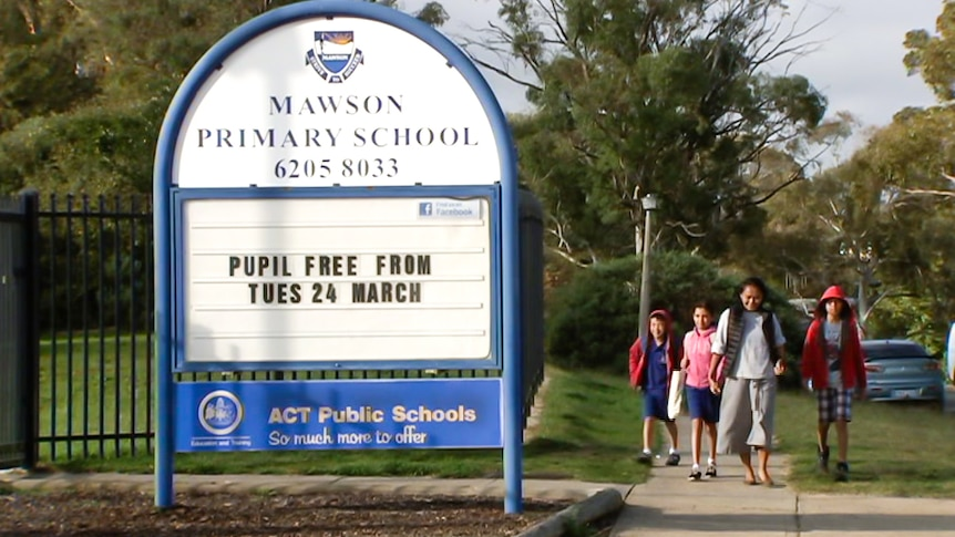 A family walks past a school sign.