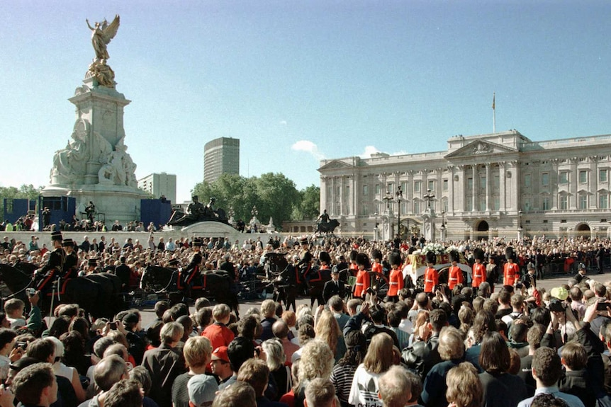 You look from behind a large crowd gathered at the front gates of Buckingham Palace with Princess Diana's coffin passing by.