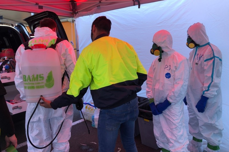 A group of people in hazmat suits and high-vis.