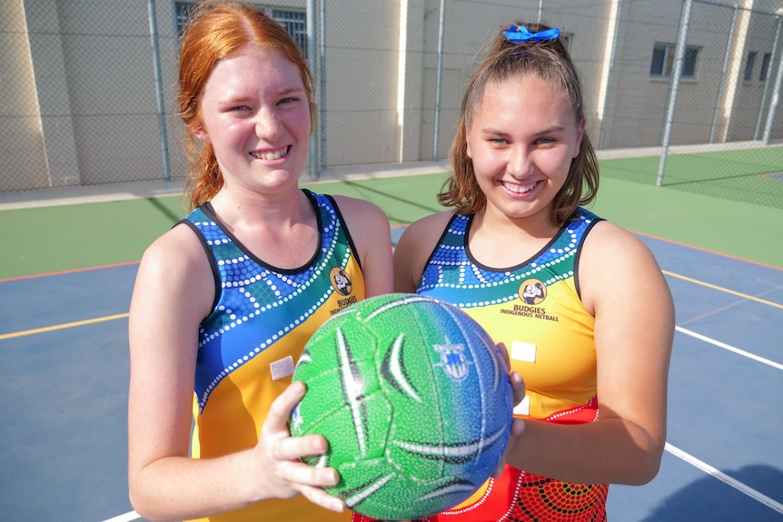 Poppy and Mercedes in their colour Australian Indigenous Budgies uniform holding a netball and smiling.