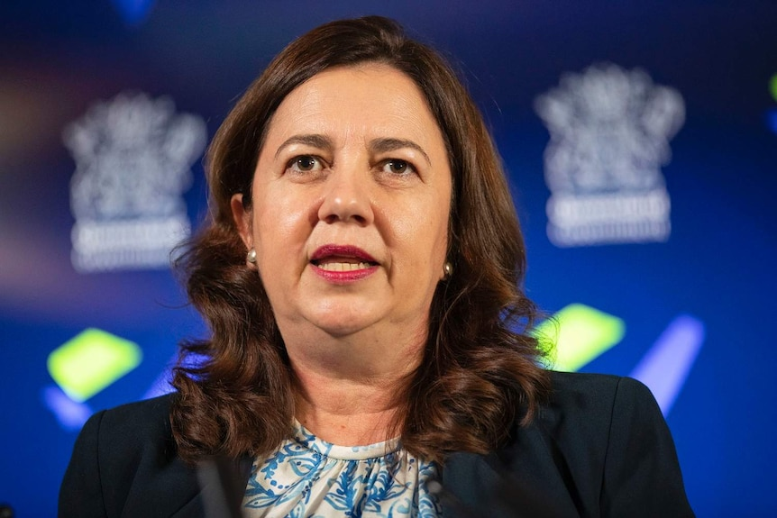 Ms Palaszczuk speaks at a press conference in front of a blue screen with the Queensland government logo.