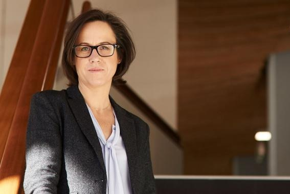 A portrait photo of a woman in a grey suit jacket and glasses.