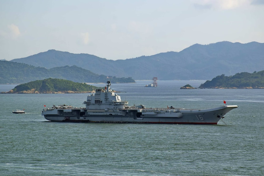 A large aircraft carrier sits in the middle of a harbour with various inlets and mountainous peninsulas shown in the distance.