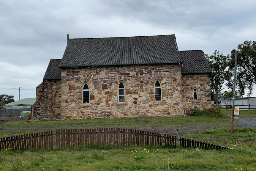 A stone church built in the 1840s, surrounded by green lawn.